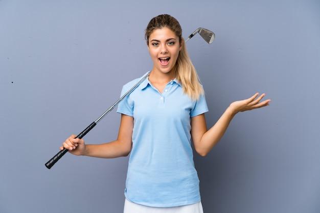Golfspelermeisje over grijze muur met geschokte gelaatsuitdrukking