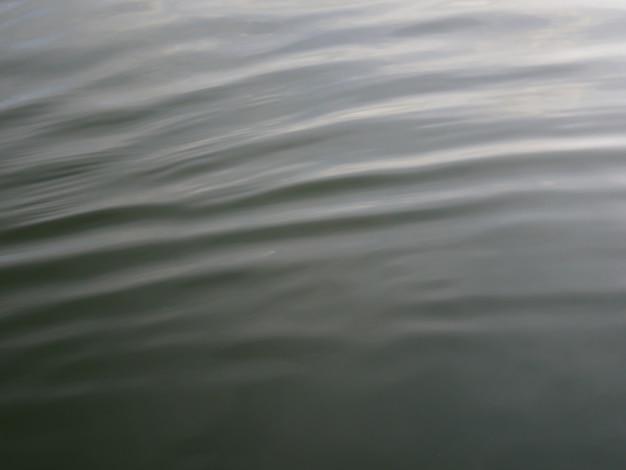 Golftextuur op de rivier met het wijzen van op wolken in de waterspiegel.