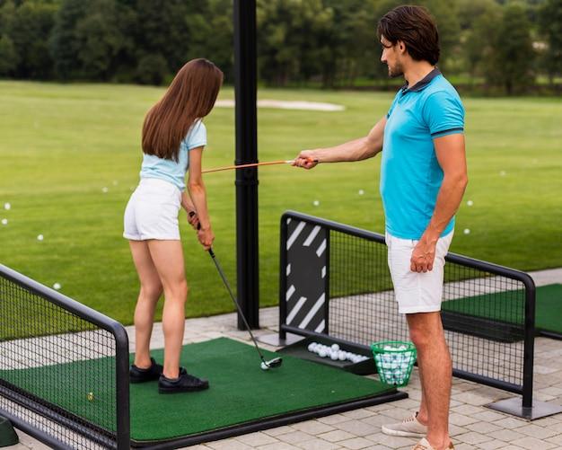 Golftrainer die een beginner onderwijst