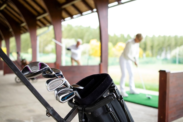 Golfuitrusting en golfclubs terwijl op de achtergrond golfers lange shots oefenen.