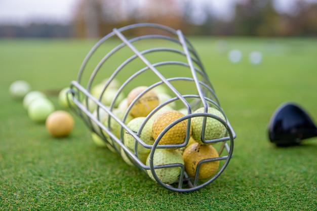 Golfuitrusting op groene golfbaan, ballen en stokken klaar om te spelen