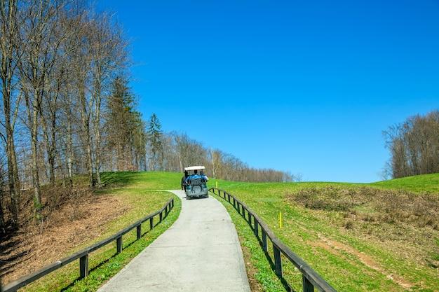 Golfvrachtwagen die door het pad op de golfbaan in otocec, slovenië rijdt