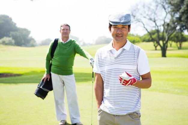 Golfvrienden die bij camera glimlachen