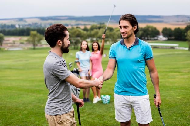 Golfvrienden die handen op golfgebied schudden