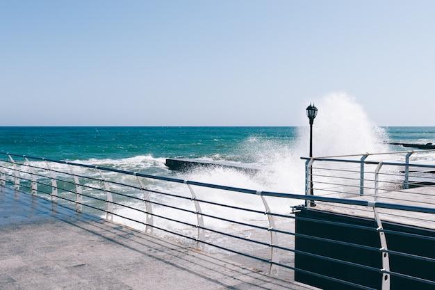 Golven breken op de pier op een zonnige dag