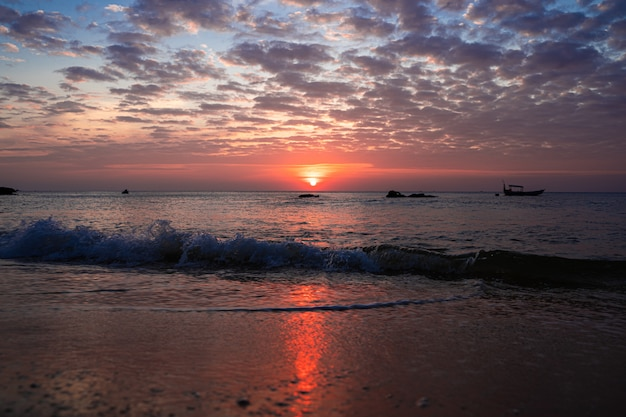 Golven die bij het strand tijdens een zonsondergang aankomen