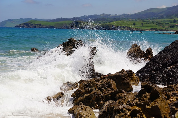 Golven die op rotsen breken met een blauwe oceaan erachter