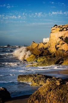 Golven die 's middags de klif in de kust van marokko raken