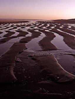Golven gemaakt op het zand door het zwemwater van het strand.
