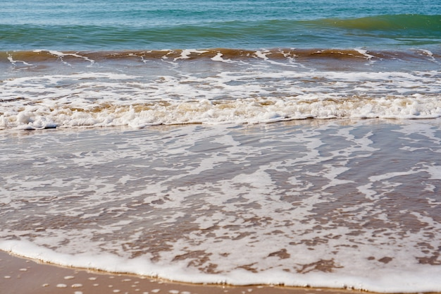 Golven met schuim op een zandstrand.