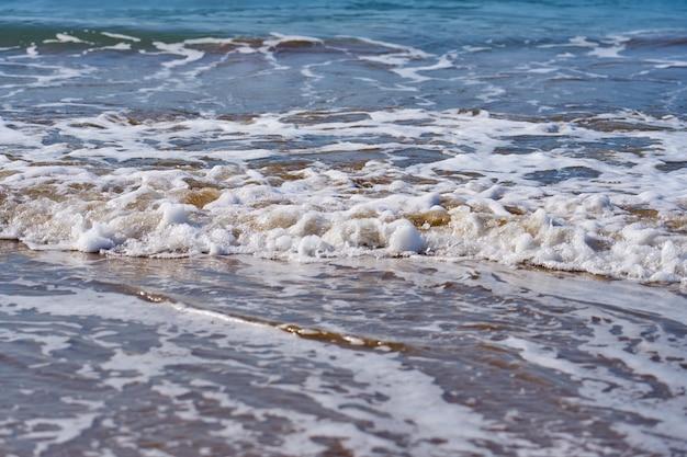 Golven met schuim op het zandstrand van de middellandse zee die tot achter de horizon reiken