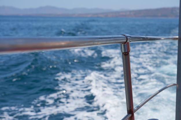 Golven met schuim overboord het schip met de kust op de achtergrond.