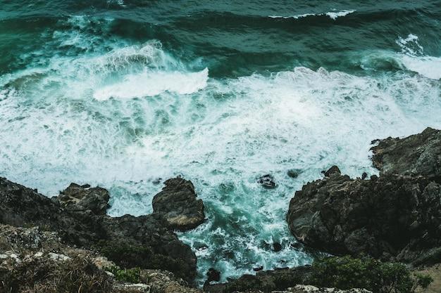Golven raken de rotsen aan de oever van de oceaan