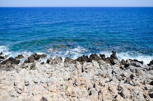 Golven slaan tegen de rotsachtige kust in rethymnon