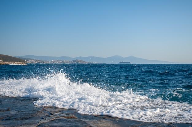 Golven snijden door de pier, de golven interfereren met zwemmen, onveilig aan het water, gevaarlijke golven