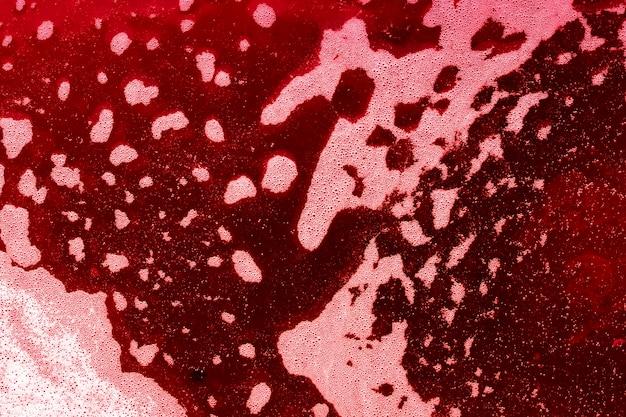 Golven van bubbels op rood gekleurde vloeistof