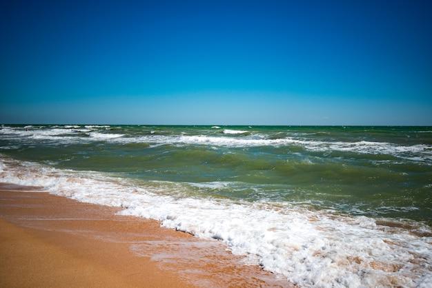 Golven van een lawaaierige zee met blauw water spatten op een zandstrand op een zonnige warme zomerdag