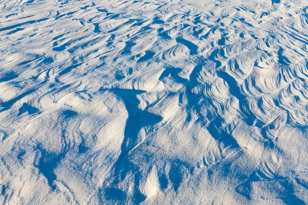 Golvend gestreept oppervlak van sneeuw, gevormde diepe sneeuwlaag, winteraard bij zonnig weer
