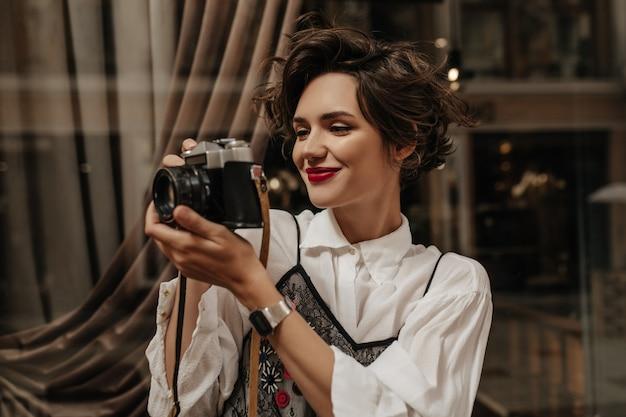 Golvend-haired vrouw met rode lipa in lichte blouse met camera in café. stijlvolle vrouw die met donkerbruin haar foto binnen maakt.