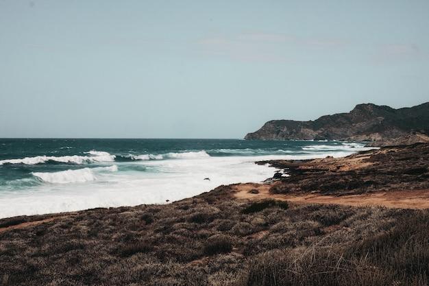 Golvende oceaan met rotsformaties onder de blauwe hemel
