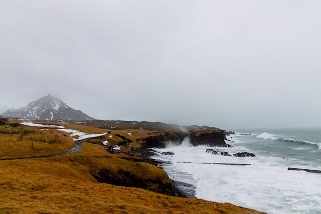Golvende zee omgeven door rotsen bedekt met sneeuw en gras onder een bewolkte hemel in ijsland