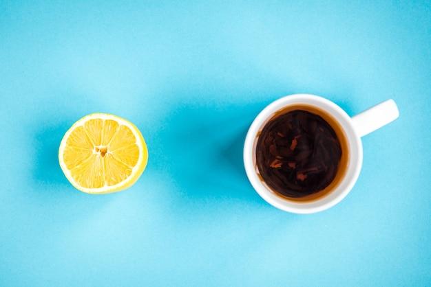 Gom met citroen en mok thee op blauwe achtergrond. reiniging en bescherming van tanden.