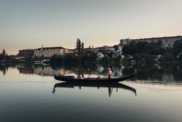 Gondel in een rivier met stad op de achtergrond met mooie avondlucht