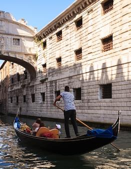 Gondelier onder de brug der zuchten in venetië