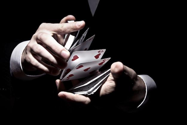 Goochelaar die de kaarten op een koele manier in de schijnwerpers schudt