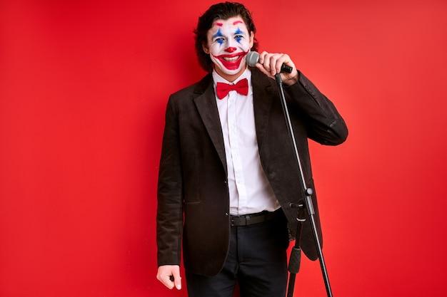 Goochelaar die de uitvoering begint en voor een publiek spreekt met een microfoon. man in zwart pak met kleurrijke make-up op gezicht geïsoleerd op rode achtergrond