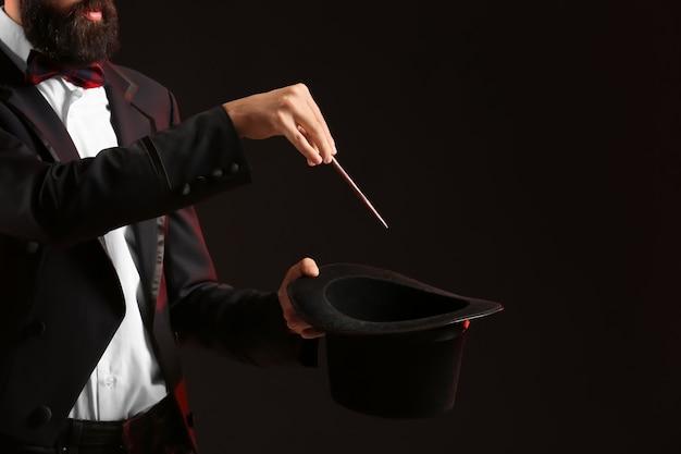 Goochelaar die trucs laat zien op een donkere ondergrond