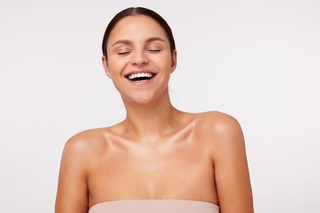 Goog op zoek naar positieve jonge donkerharige dame die natuurlijke make-up draagt tijdens het poseren, gelukkig lachend met gesloten ogen, in een hoge geest