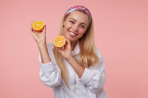 Goog op zoek yound blonde vrouw poseren met helften van oranje in haar handen, vrolijk glimlachend, gekleurde hoofdband en wit overhemd dragen