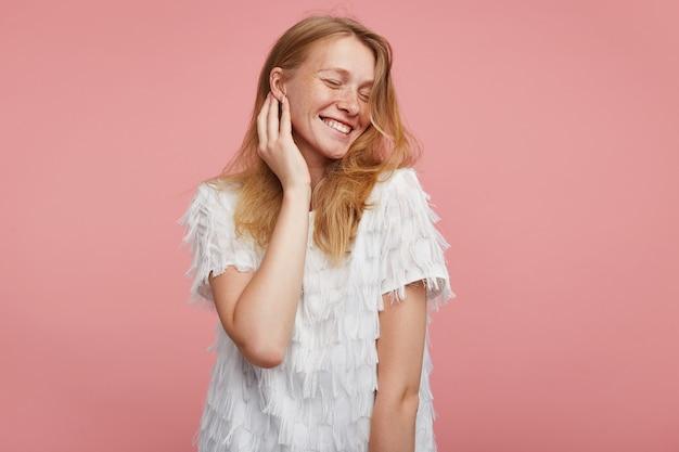 Goog uitziende jonge vrolijke mooie vrouw met foxy haar zachtjes haar gezicht aanraken met opgeheven hand terwijl ze aangenaam lacht met gesloten ogen, geïsoleerd op roze achtergrond
