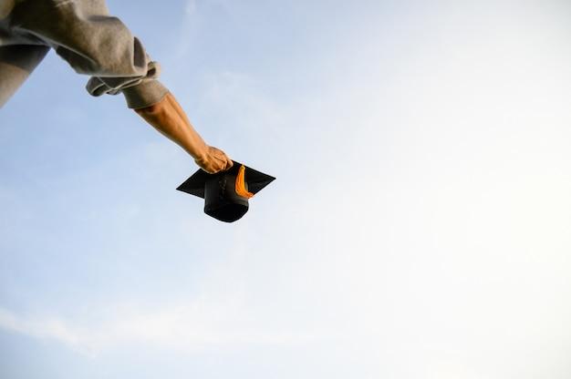 Gooi een zwarte hoed van afgestudeerden in de lucht.