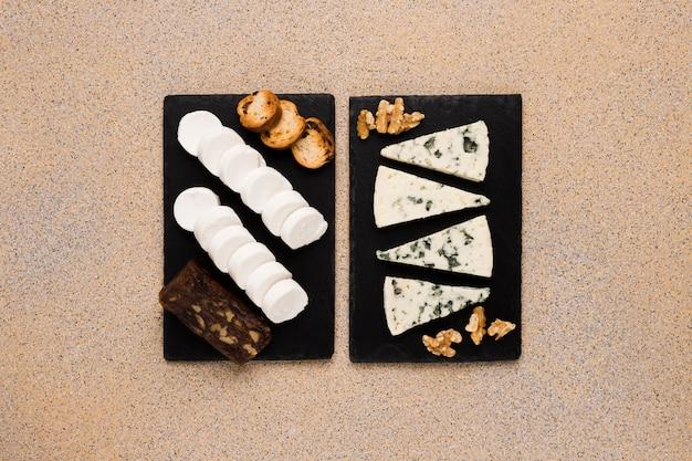 Gorgonzola-kaasplakken en walnoot met geitenkaas; bruine kaas en brood op zwarte leisteen over gestructureerd behang