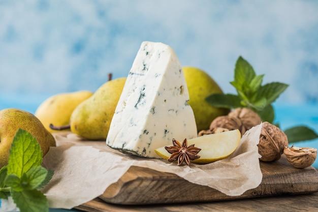 Gorgonzola picant italiaanse blauwe kaas, gemaakt van magere koemelk in noord-italië. stukje blauwschimmel kaas danablu, roquefort met peer en walnoten