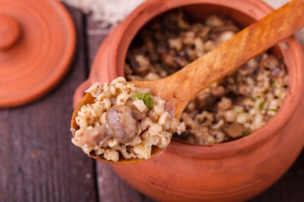 Gortpap met champignons in een aarden pot