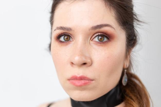 Gothic, make-up, mode en mensen concept - jonge stijlvolle mooie vrouw met witte huid en rode lippen op wit oppervlak