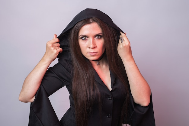 Gotische jonge mooie vrouw in het kostuum van heksenhalloween
