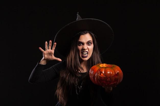 Gotische jonge vrouw in het kostuum van heksenhalloween die zich over zwarte achtergrond bevindt. heksenvrouw die verschrikkingspompoen houdt.