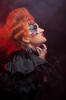 Gotische roodharige heks. donkere vrouw. artistieke make-up. halloween-foto.
