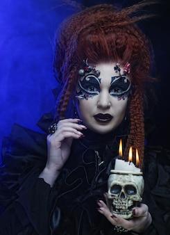 Gotische vampier redhair vrouw met schedel.