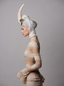 Gotische vrouw met historische kanten jurk met hoorns op haar hoofd, accultisme, halloween-beeld