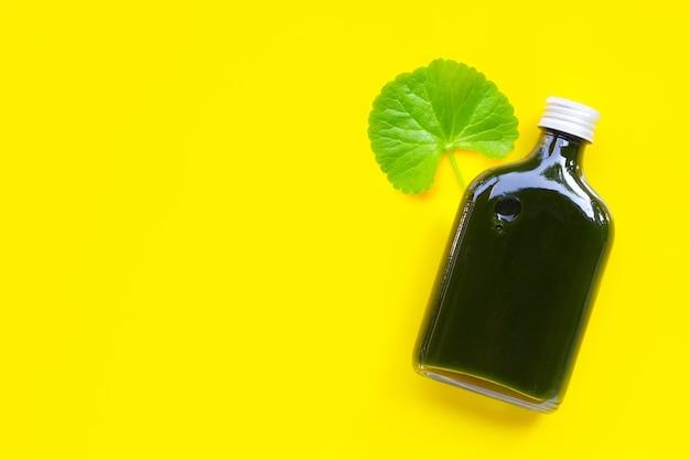 Gotu-kola laat sap voor de gezondheid achter op geel