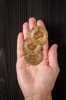 Goud bitcoin in handen bij de vrouw tegen de achtergrond van een houten tafel
