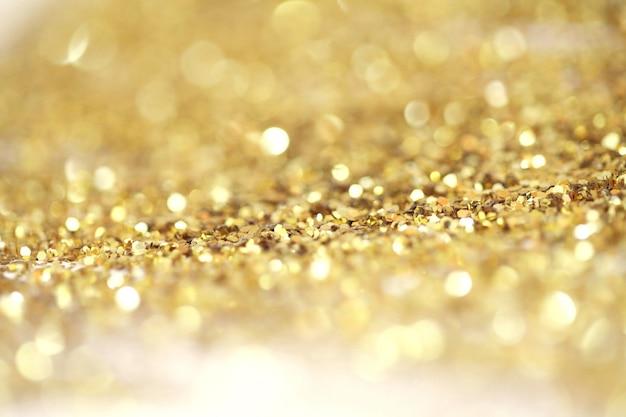 Goud (brons) glitter glans stippen confetti. abstract licht knipperen sparkle defocus achtergrondkleur.
