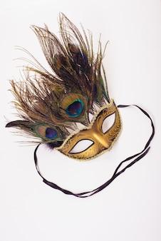 Goud een carnaval masker met veren op wit