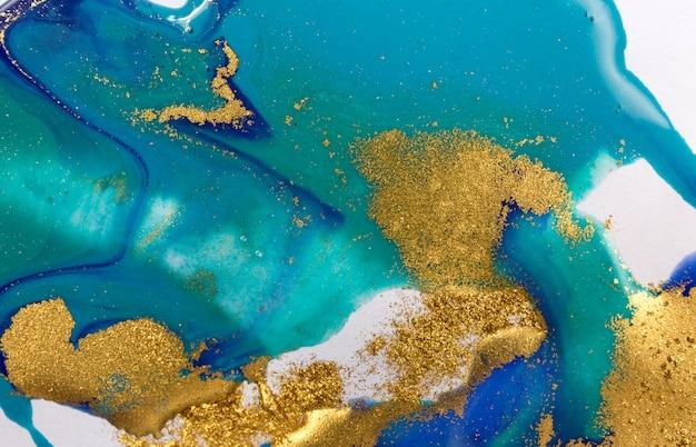 Goud en blauw gemengde inkt spetterde op witboek achtergrond.