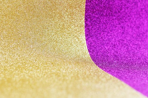 Goud en paars gebogen gliterpapier. ruimte voor tekst.